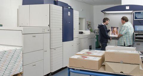Zwei Männer betrachten in der Druckerei ein Poster